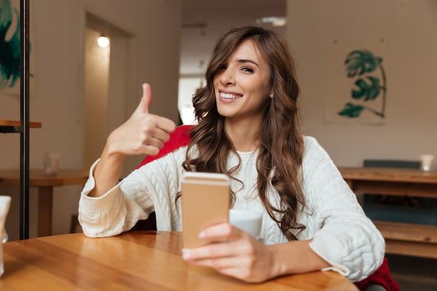 Portrait of a joyful woman holding mobile phone