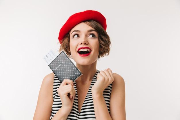 Portrait of a joyful woman wearing red beret holding passport