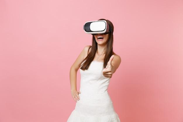 Ritratto di donna gioiosa in abito bianco, cuffia di realtà virtuale che mostra pollice in su