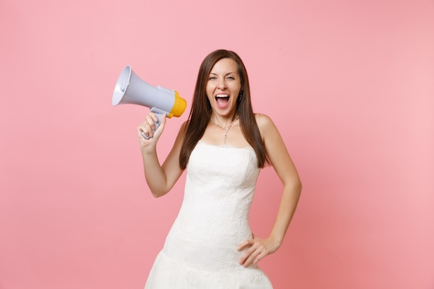 Portrait of joyful woman in white lace white dress screaming standing and holding megaphone
