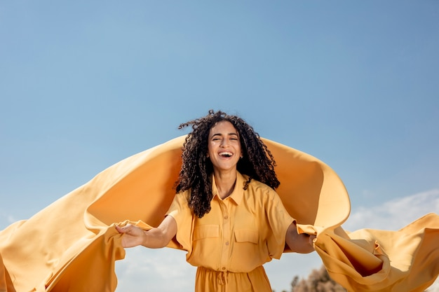 Portrait of joyful woman with yellow cloth in nature