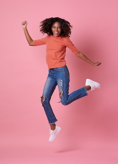 Portrait of a joyful young african woman in orange shirt jumping and celebrating over pink.