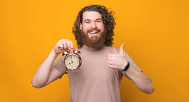 Portrait of joyful young bearded man with long hair showing thumb up gesture and alarm clock