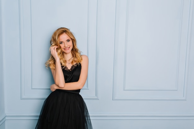 Portrait of joyful young blonde woman wearing elegant black lace dress. blue wall. her mouth opened, touching her face. she has long blonde wavy hair.