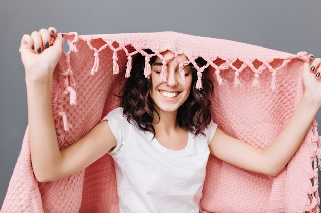 Portrait joyful young brunette woman in pajamas having fun under pink blanket. smiling with closed eyes, expressing true positive emotions, relaxing at home