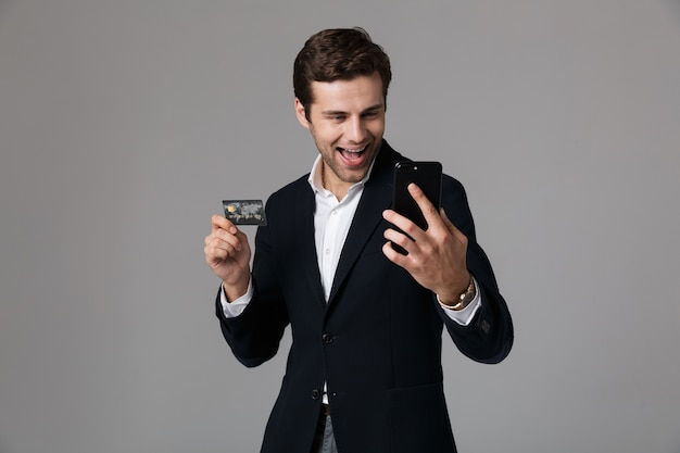 Portrait of a joyful young businessman dressed in suit isolated over gray wall, using mobile phone, showing credit card