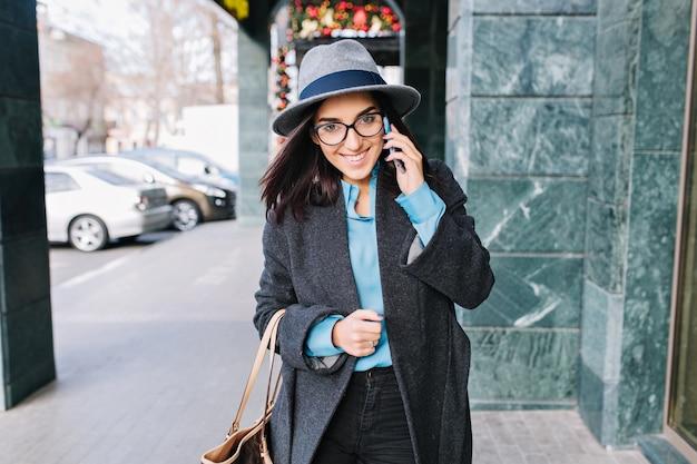 肖像画うれしそうな若い実業家の街の通りを歩いて、笑顔で電話で話します。魅力的なモデル、グレーのコート、帽子、黒のメガネ、本当の喜び。