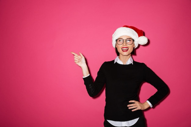 Portrait of a joyful young businesswoman with santa hat