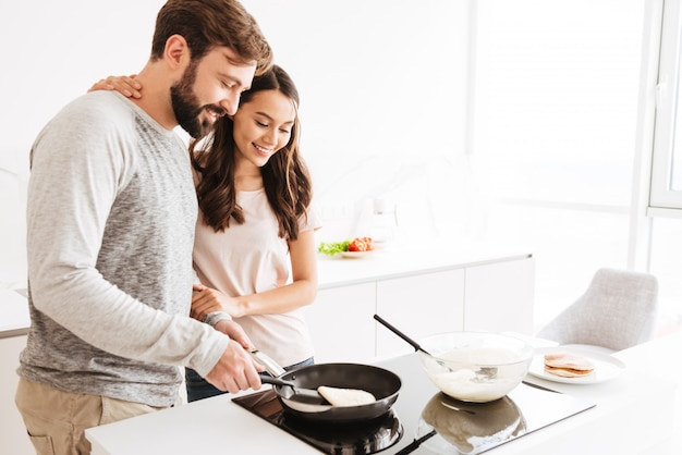 Portrait of a joyful young couple cooking pancakes