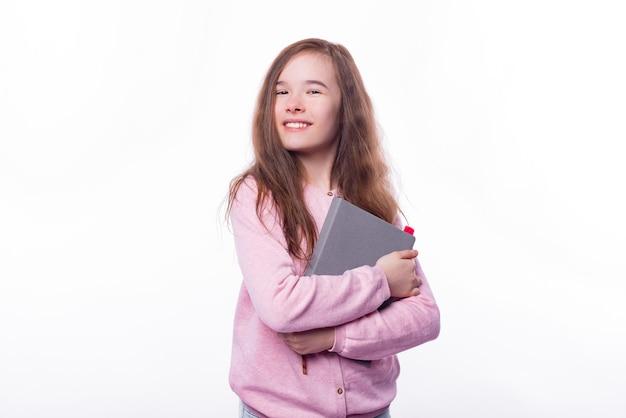 Portrait of joyful young girl holding planner over white