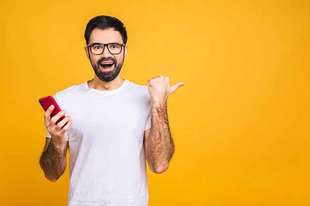 Portrait of a joyful young man holding a mobile phone isolated on yellow background, celebrating victory.