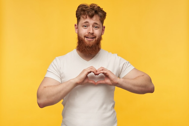 Portrait of joyful young man, wears blank t-shirt, shows heart with his arms, love gesture on yellow