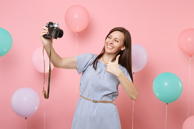Portrait of joyful young woman in blue dress doing selfie on retro vintage photo camera showing thumb up on pink background with colorful air balloons. birthday holiday party people sincere emotions.