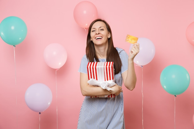 Portrait of joyful young woman in blue dress holding credit card and red box with gift present on pastel pink background with colorful air balloons. birthday holiday party, people sincere emotions.