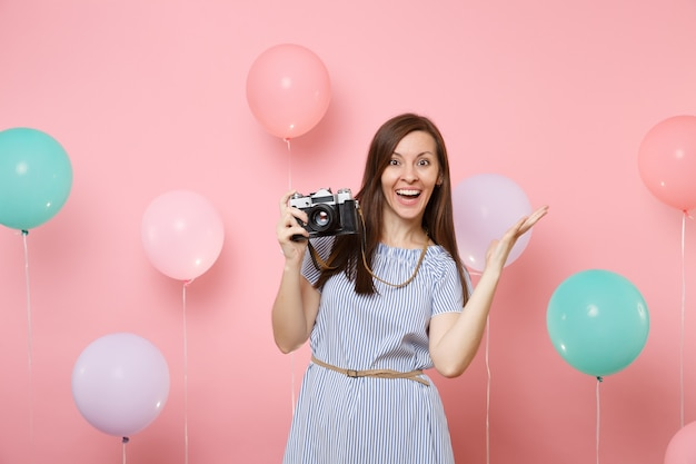 Portrait of joyful young woman in blue dress holding retro vintage photo camera spreading hands on pink background with colorful air balloons. birthday holiday party people sincere emotions concept.
