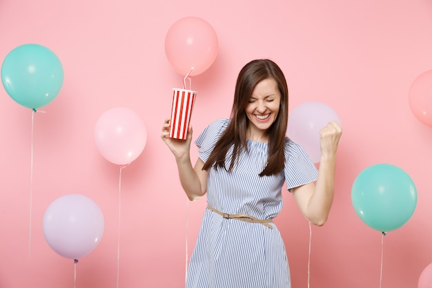 Portrait of joyful young woman in blue dress with closed eyes doing winner gesture saying yes holding plastic cup of cola or soda on pink background with colorful air balloons. birthday holiday party.