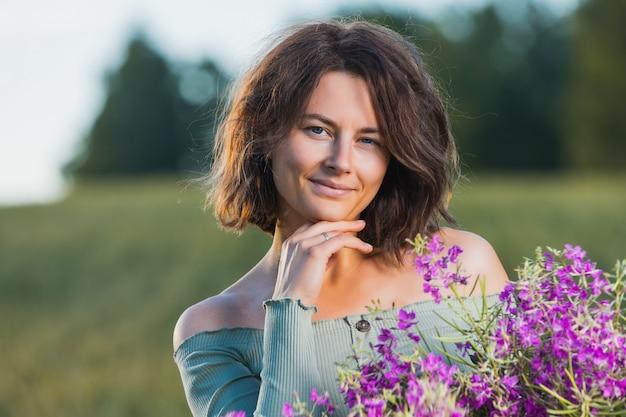紫色の花の花束と青いドレスのポートレートうれしそうな若い女性ブルネットは笑顔し、フィールドで1日をお楽しみください。スタイリッシュな流行に敏感な女性。屋外の雰囲気のあるライフスタイルの写真