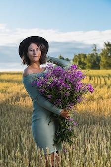 ウォーキングとフィールドの美しい自然で休んで紫の花の花束と青いドレスの肖像画うれしそうな若い女性ブルネット。スタイリッシュな流行に敏感な女性。屋外の雰囲気のあるライフスタイルの写真
