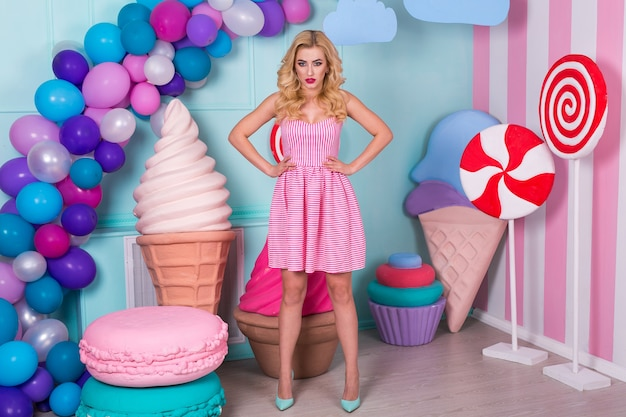 Portrait of joyful young woman  in pink dress on background decorated with huge candies and ice cream. barbie