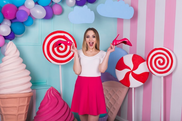 Portrait of joyful young woman  in pink dress on background decorated with huge candies and ice cream