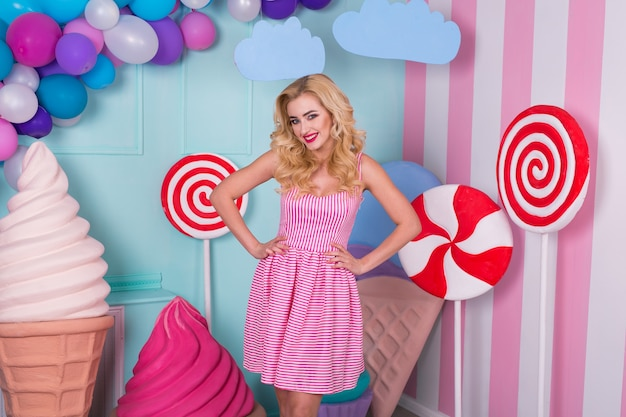 Portrait of joyful young woman  in pink dress on background decorated with huge candies and ice cream.