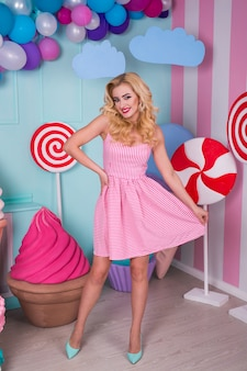 Portrait of joyful young woman  in pink dress on decorated with huge candies and ice cream.