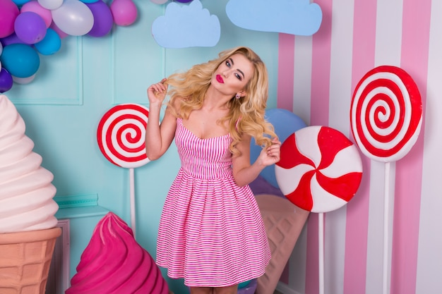 Portrait of joyful young woman  in pink dress with huge candies and ice cream.