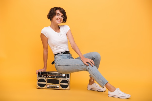 Portrait of a joyful young woman sitting record player