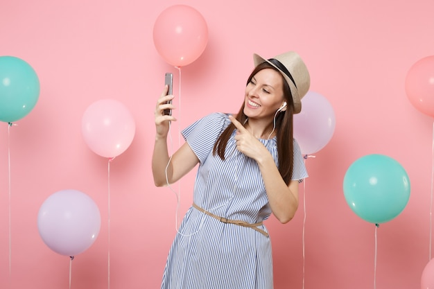 Portrait of joyful young woman in straw summer hat blue dress with mobile phone and earphones listening music making video call on pink background with colorful air balloons. birthday holiday party.