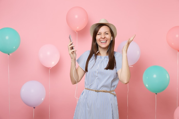 Portrait of joyful young woman in straw summer hat and blue dress with mobile phone and earphones listening music spreading hand on pink background with colorful air balloons. birthday holiday party.