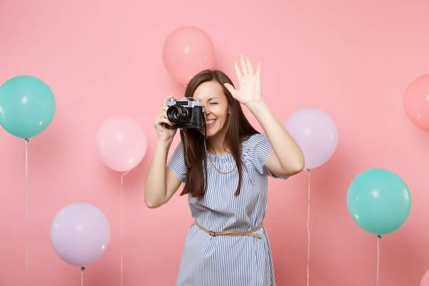 Portrait of joyful young woman wearing blue dress take picture on retro vintage photo camera showing hand on pink background with colorful air balloons. birthday holiday party people sincere emotions.