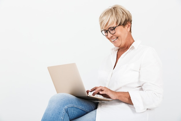 Portrait of joyous adult woman wearing eyeglasses smiling while sitting with laptop computer isolated over white wall in studio