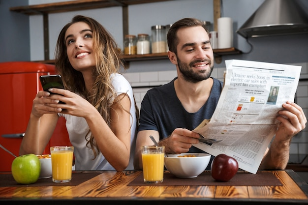 Portrait of joyous couple man and woman sitting at table in kitchen while having breakfast at home in the morning
