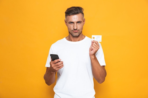 Portrait of joyous guy 30s in white t-shirt holding mobile phone and credit card isolated on yellow