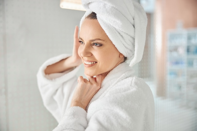 Portrait of a joyous lady with her hair wrapped in a bath towel looking away