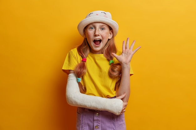 Portrait of joyous redhead girl waves palm in hello gesture, says hi to parents, being in good mood, wears summer outfit, cast on broken arm after falling during rollerblading, isolated on yellow wall