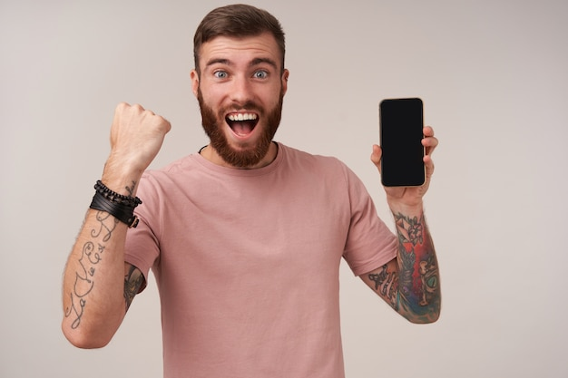 Portrait of joyous tattooed unshaved brunette guy keeping mobile phone in hand with wide cheerful smile, raising fist in yes gesture, isolated on white