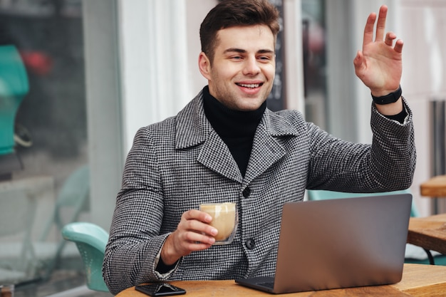 Portrait of joyous young guy smiling and waving hand having appointment with friend in street cafe