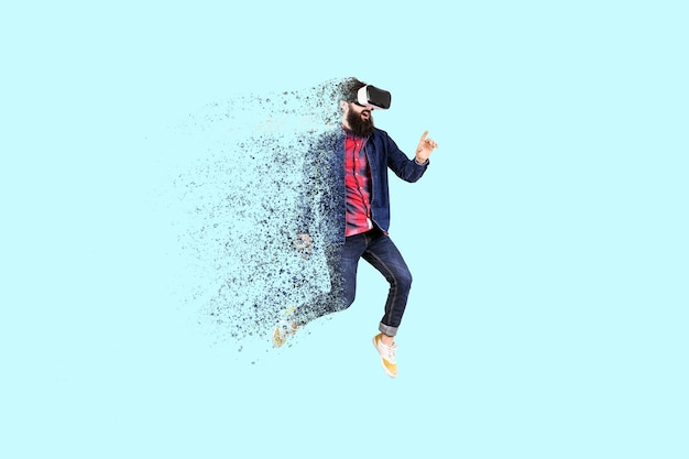 Portrait of a jumping bearded hipster in glasses of virtual reality, man dispersing and disintegrating into particles