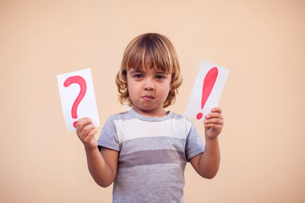 Portrait of kid boy holding cards with exclamation point and question mark. children and education concept