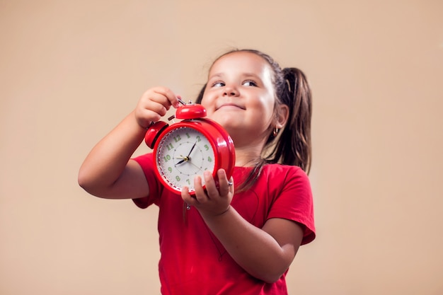 Portrait of kid boy holding red alarm clock. childhood and time management concept