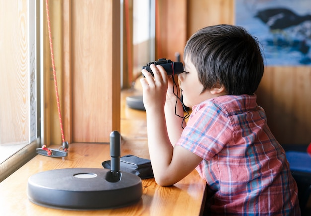 Portrait kid boy looking through of binoculars in the animals station view point.