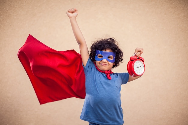 Portrait of kid boy with curly hair in costume of superhero holding alarm clock. childhood, success and time management concept