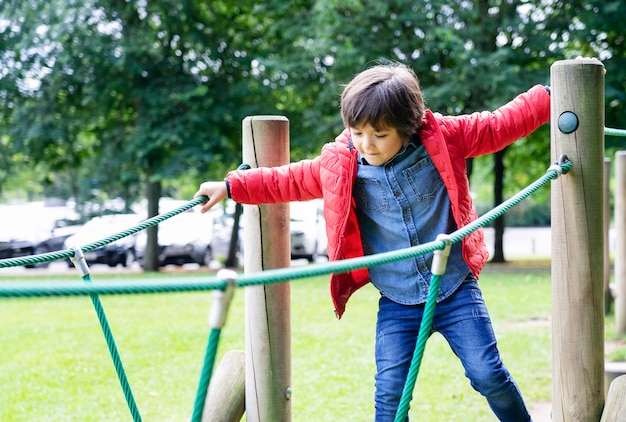Portrait kid climbing rope in the playground