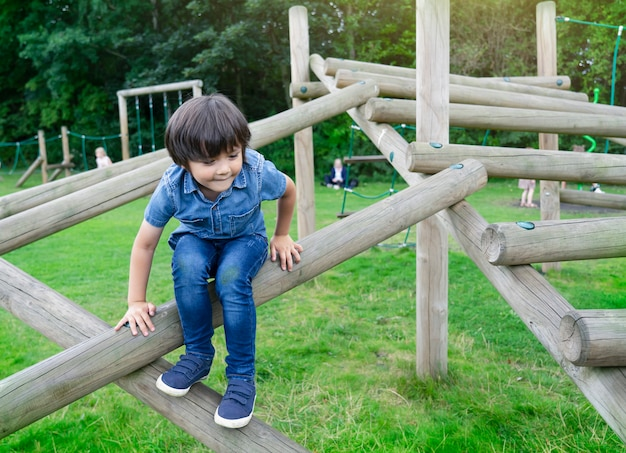 Portrait kid climbing on wooden fame in the park, child enjoying activity in a climbing adventure park on summer sunny day, little boy having fun in playground.