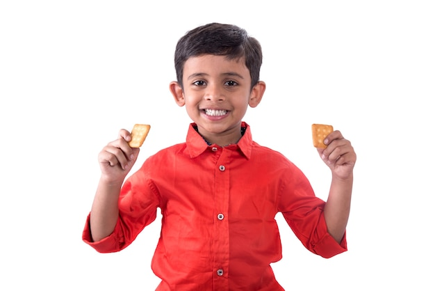 Portrait of kid eating a biscuit on white wall