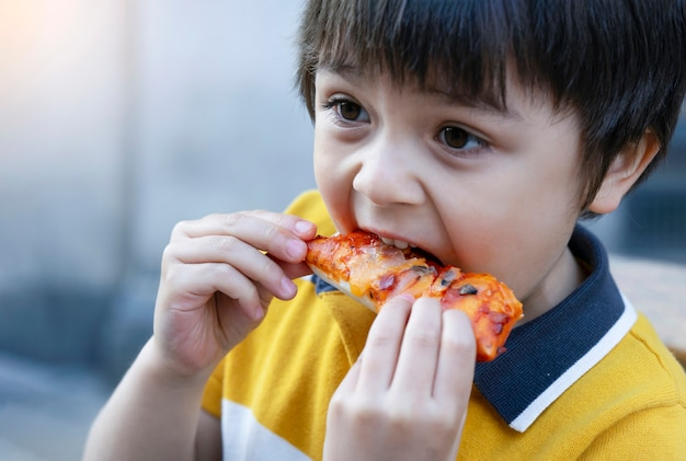 Portrait of kid eating home made pizza outdoors cafe