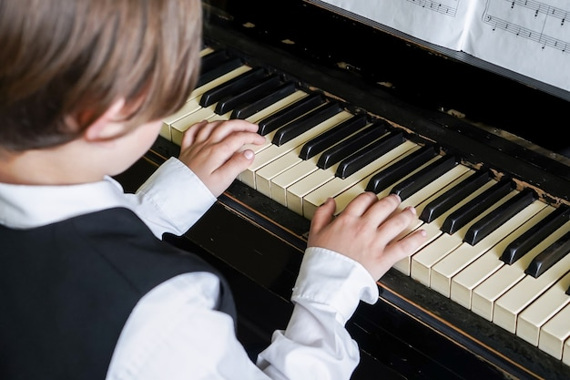 Portrait of kid playing piano, young boy learning music with an piano in musical scholl. child relaxing playing piano