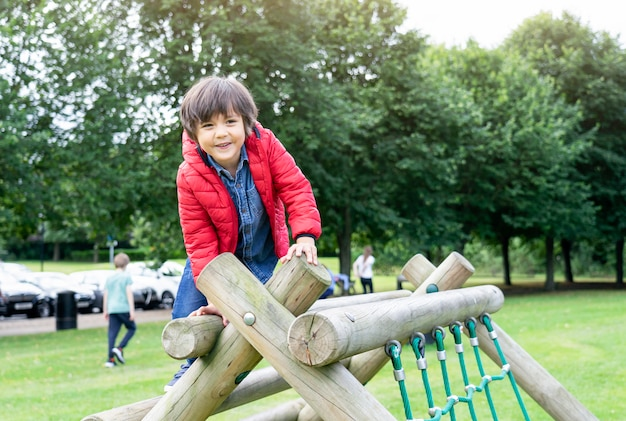 Portrait kid sitting on wooden climbing frame in the park