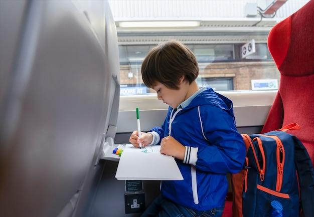 기차로 여행하는 초상화 아이, 창가에 앉아 흰 종이에 아이 그리기 만화. 가족 휴가에 고속 급행 열차에 어린 소년